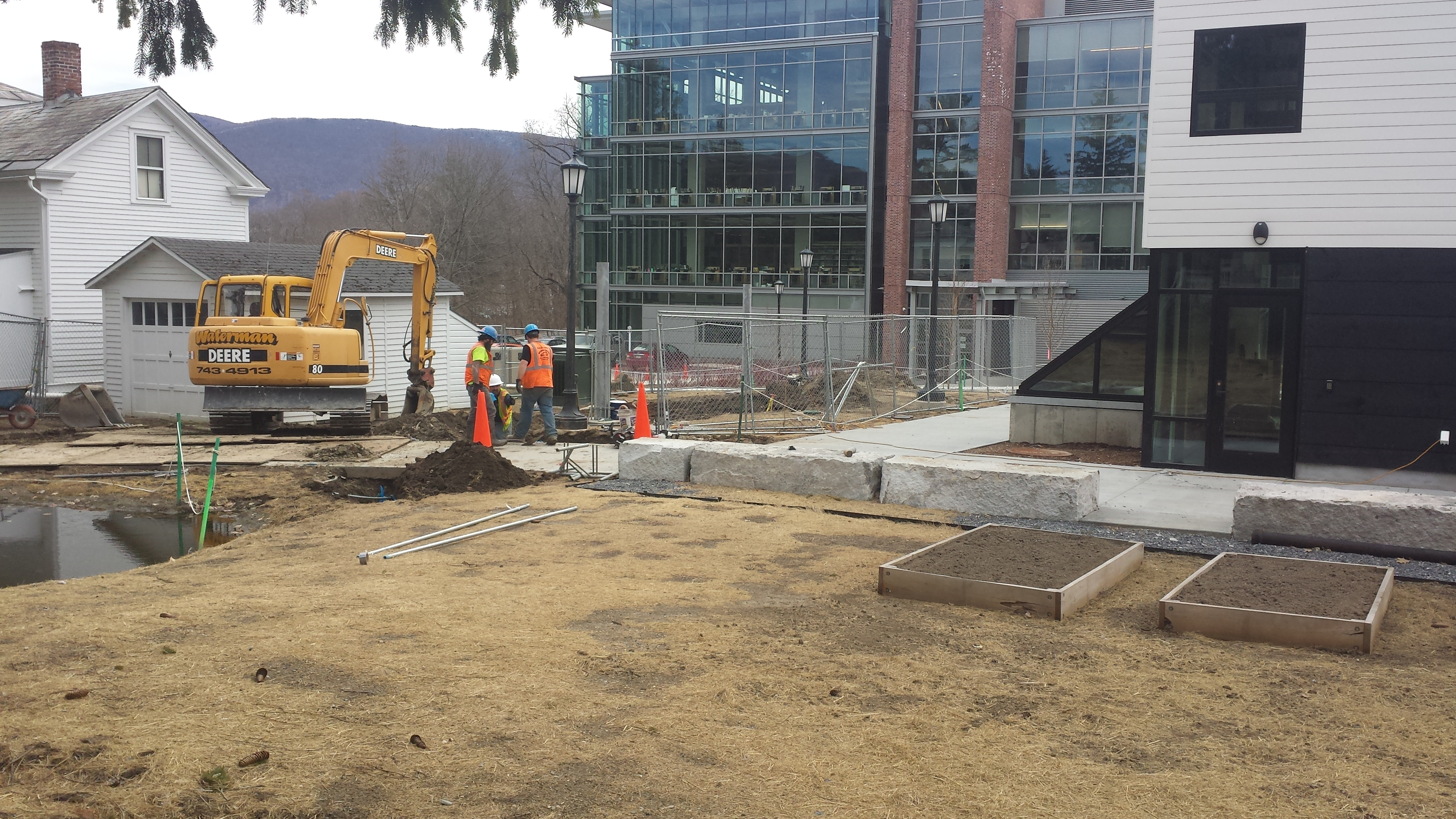 A view over the soon-to-be annual garden beds towards Sawyer Library with solar tracker construction in between.